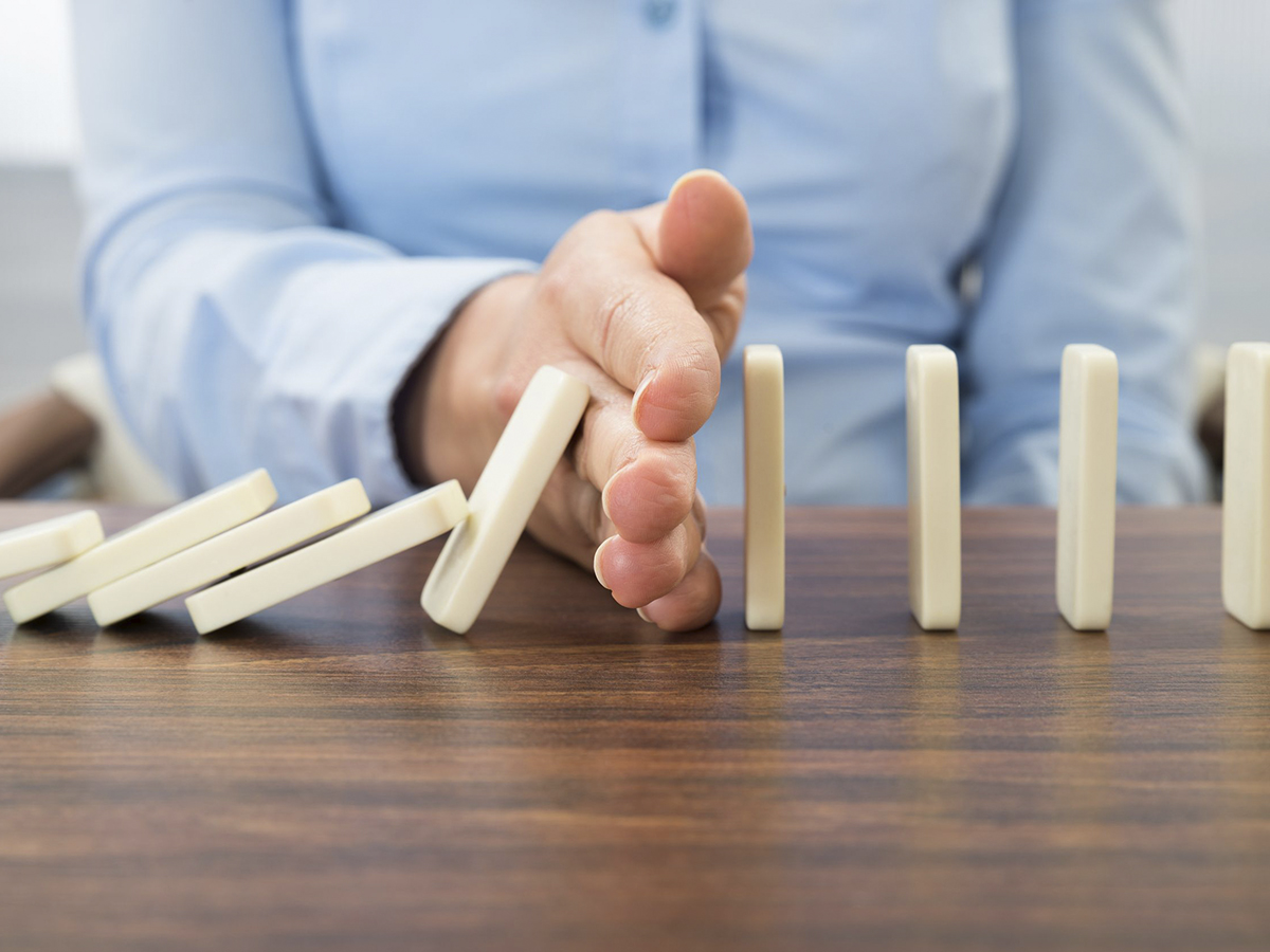 39120315 - close-up of businesswoman stopping the effect of domino with hand at desk