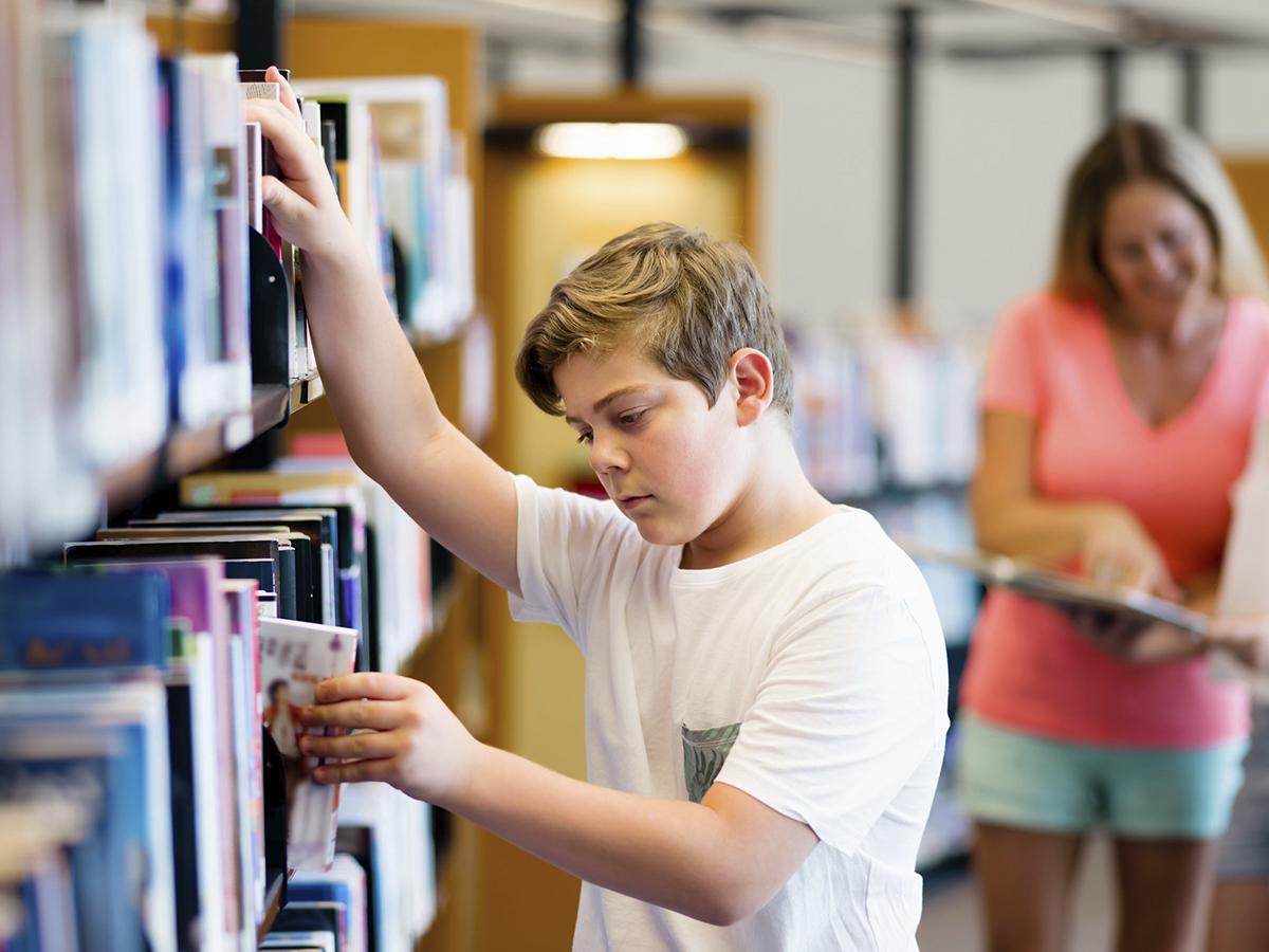 39132592 - boy in library choosing books